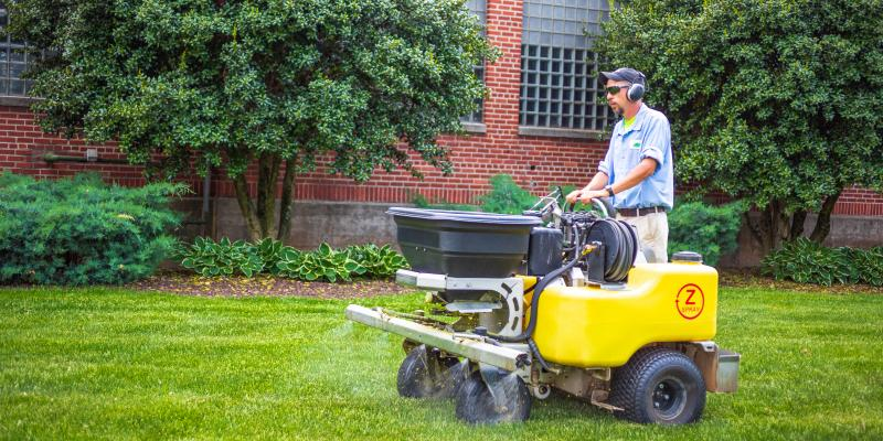 One of The Green Team's lawn care professionals using an overseeding machine to provide quality lawn care to homes in Roanoke and Charlotte.